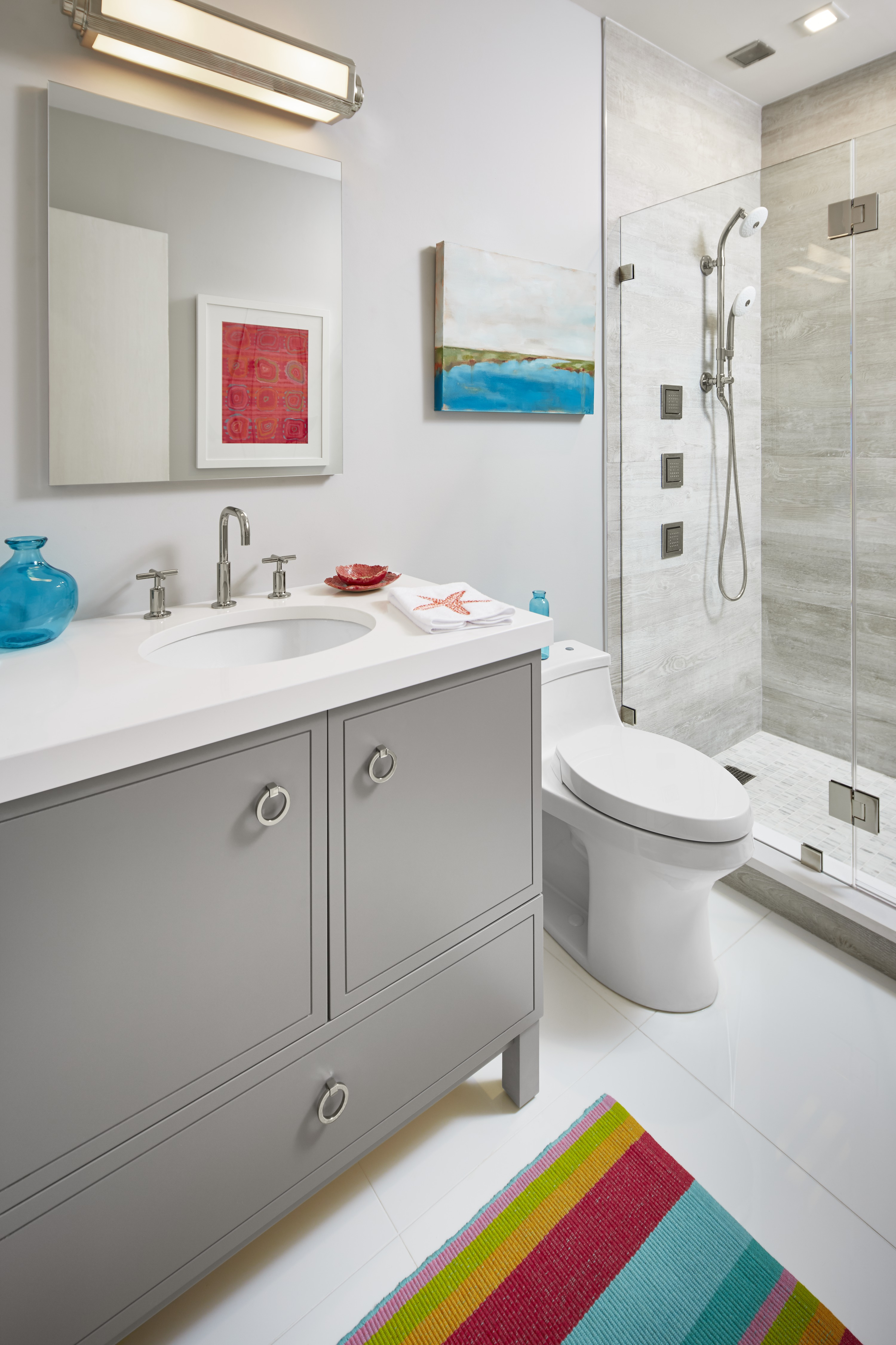 Purist Faucet     Jacquard Vanity     San Souci Touchless Toilet     Exhale Showerhead     Exhale Handshower     WaterTile Body Spray     Next to the color explosion of the sitting room, the bathroom is more subdued in grays and whites. Pops of color make their way in through small decor items.
