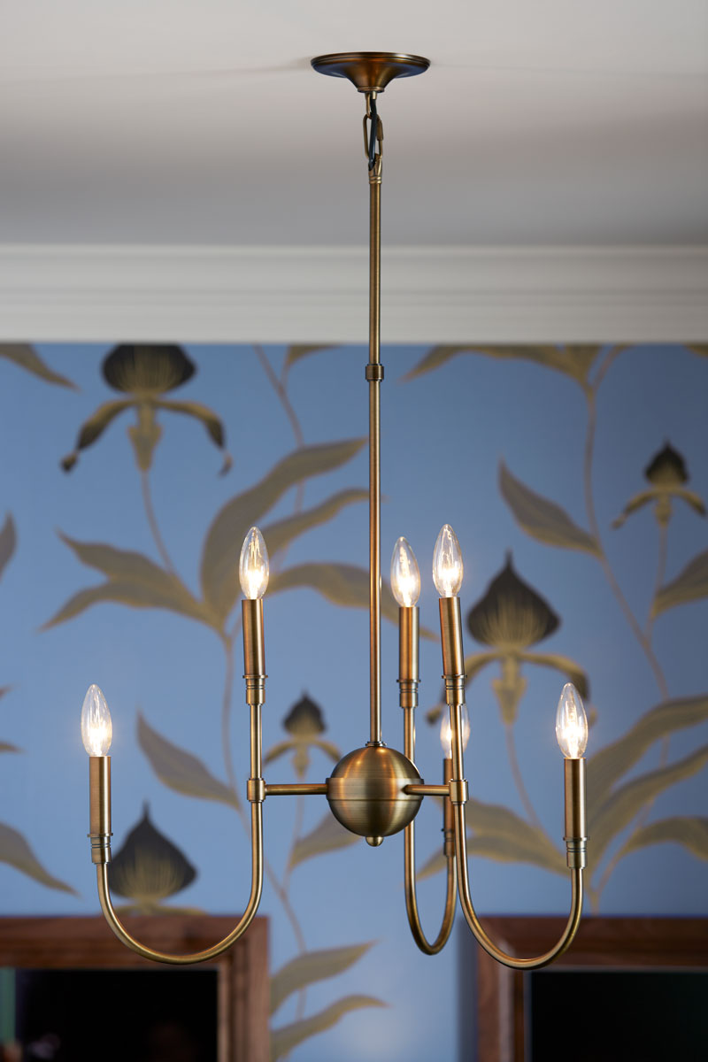 The chandelier's elegantly curved, minimalist design enhances the floral wall-covering.