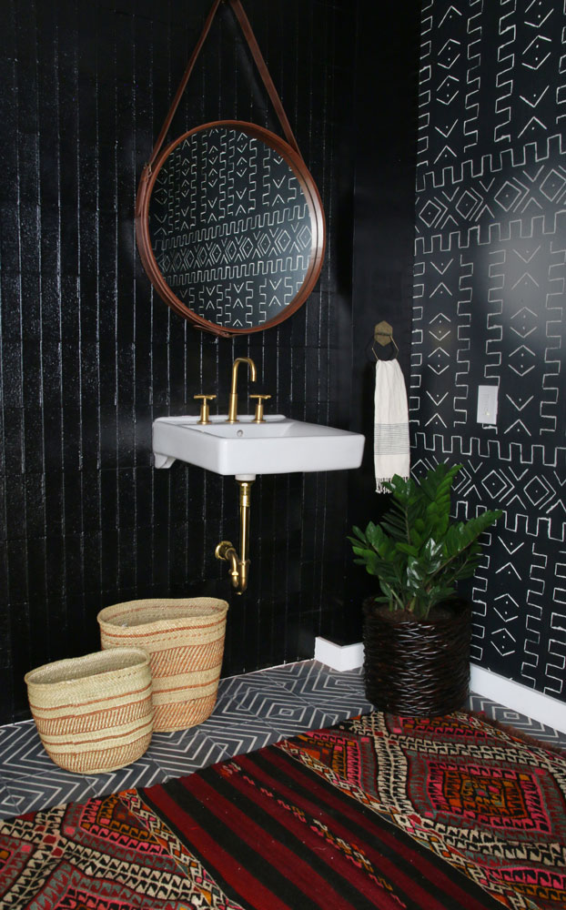 Purist faucet   Soho sink   Varied scale is essential when it comes to mixing and matching patterns. A small scale, geometric floor perfectly complements the large scale, bold patterned wallpaper. The colorful rug underfoot makes this black bathroom even more dramatic.