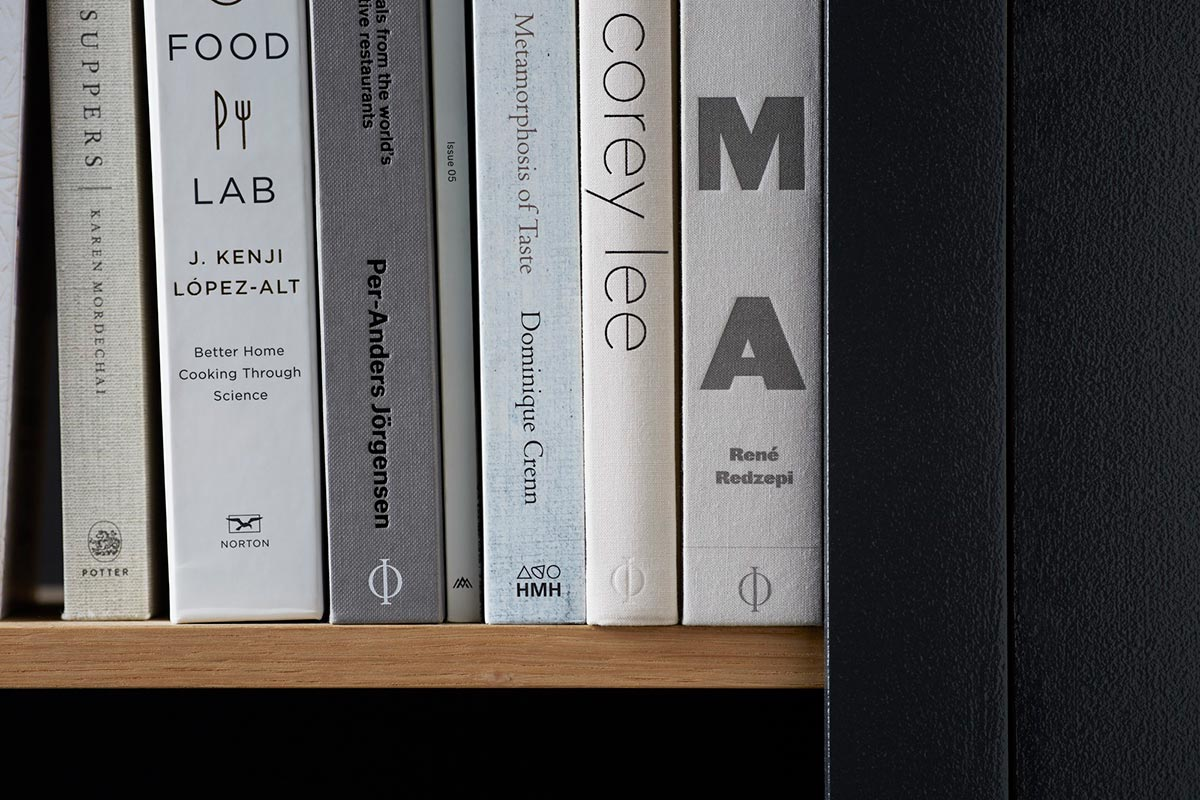 A bookshelf in the bar area introduces a thoughtful collection of books on art and taste that make the space feel organic and personal.