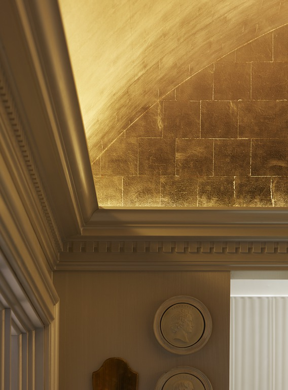 Gold leaf lends a warm glow, spotlighting ornate architectural details that play up the room's classic lines.
