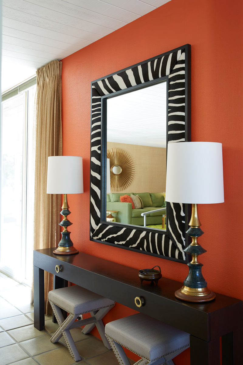 A large zebra-skin mirror pops against the orange walls of the entrance, setting the stage for the home's predominantly bright and colorful design character.