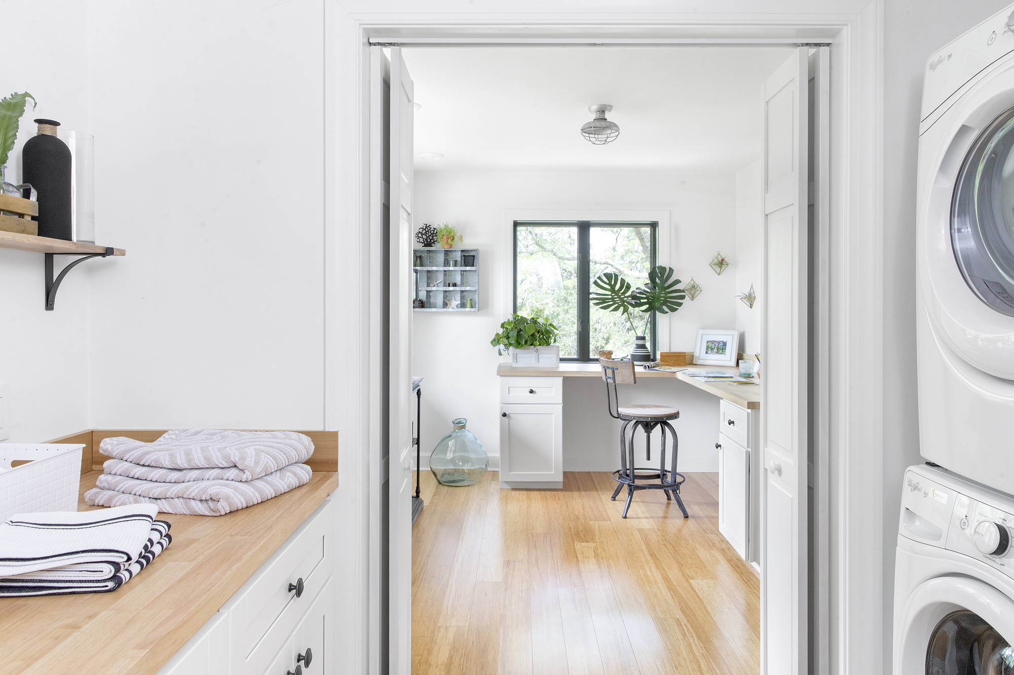 Conveniently located just off the office, the laundry room re-creates the breezy openness found throughout the home by using a simple palette of white, gray and warm wood tones.