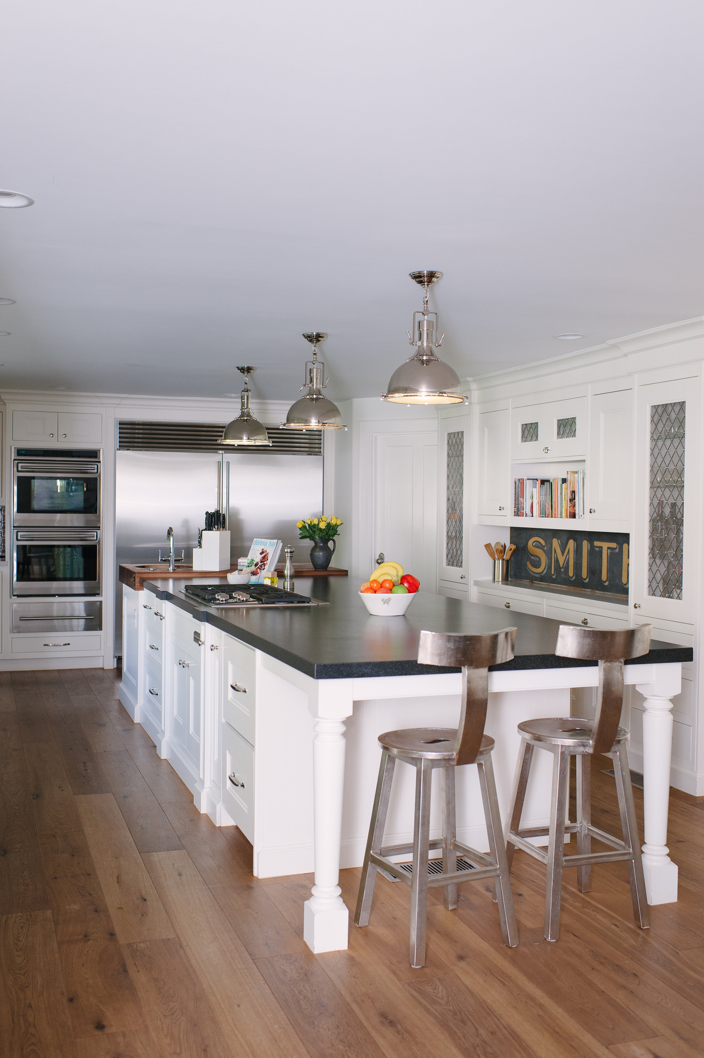 Like so many homeowners, the Smiths consider the kitchen their home base. This expansive kitchen keeps it classic with walnut floors, a double refrigerator, Silestone countertops, and custom cabinetry painted white.