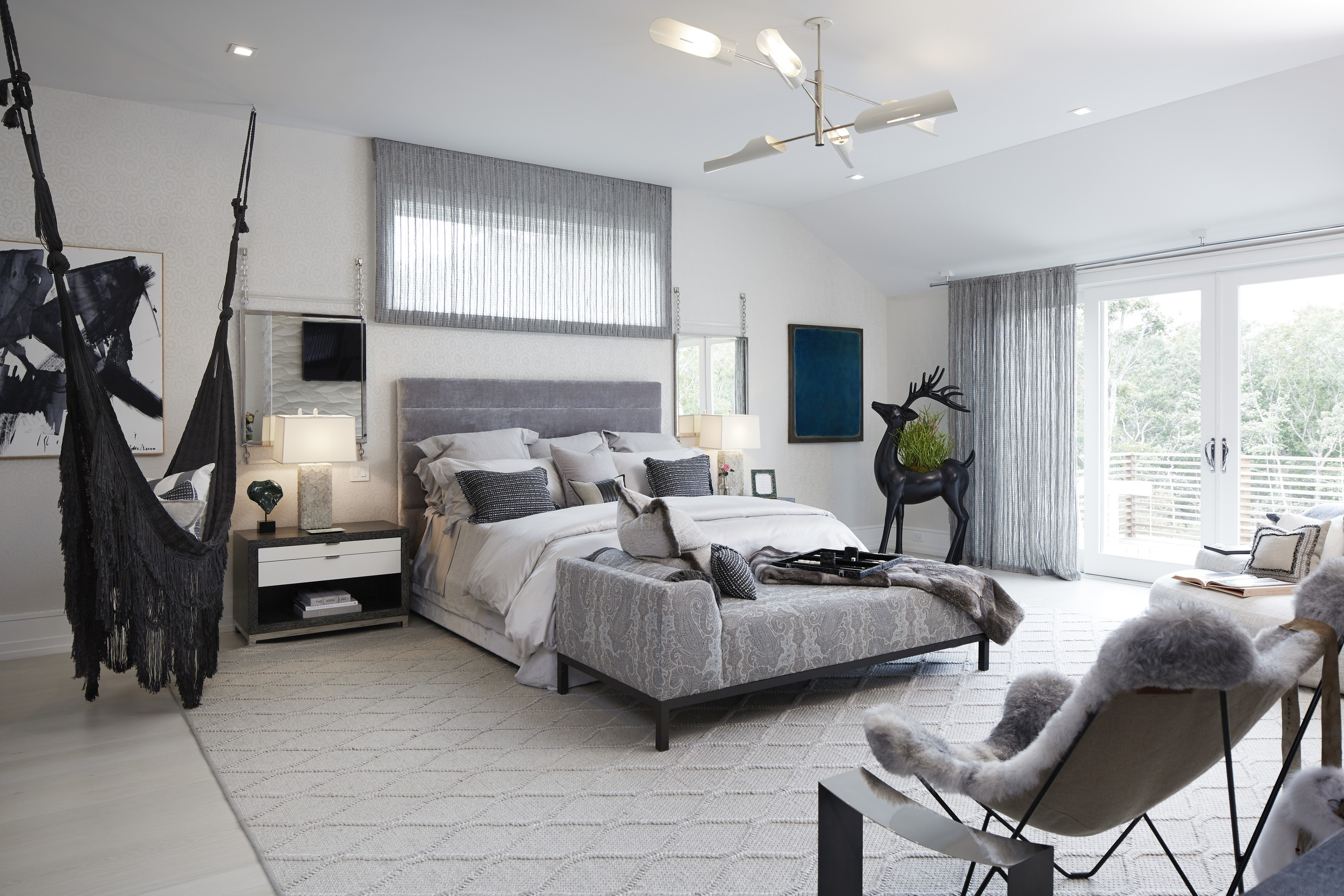 The second-floor master bedroom is all about soft edges and sumptuous textures, a nest of neutral greys and off-whites. Bold black accents bring a vibrant richness to the space.