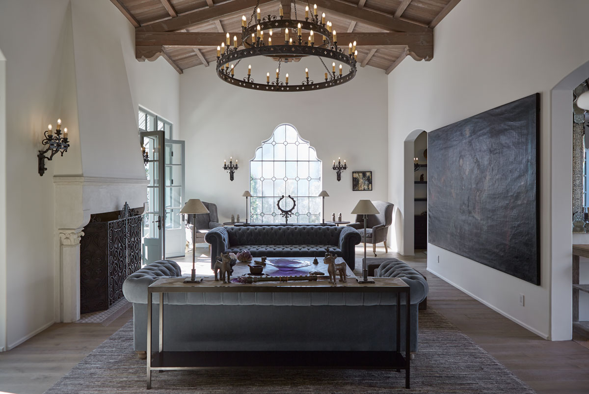 An ironwork chandelier beneath a simply coffered wood ceiling combine to bring an old-world weightiness to the living room's fireside conversation setting.