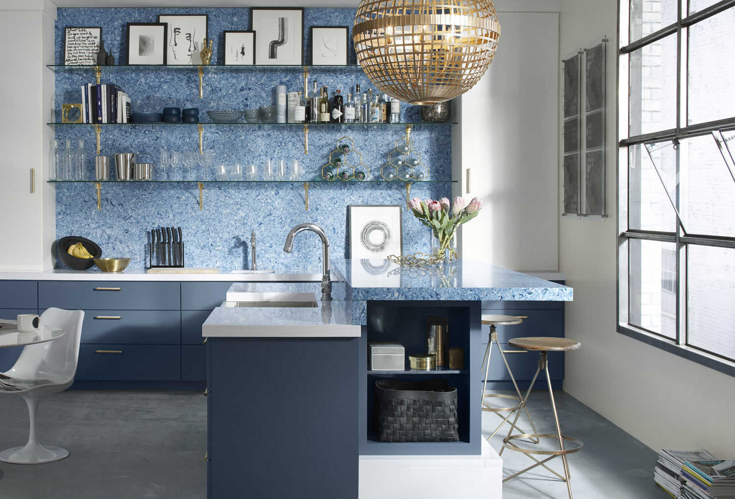 Beckon® touchless kitchen faucet     Albedo wall and breakfast counter     Using the countertop material she designed, Kerrie Kelly created a vibrant backdrop for elegant open shelving. A curated collection of glass floats above navy cabinets.