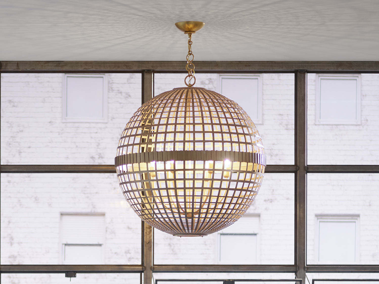 An open, airy light fixture with repeating geometric lines provides a calming contrast in a pattern-rich room.