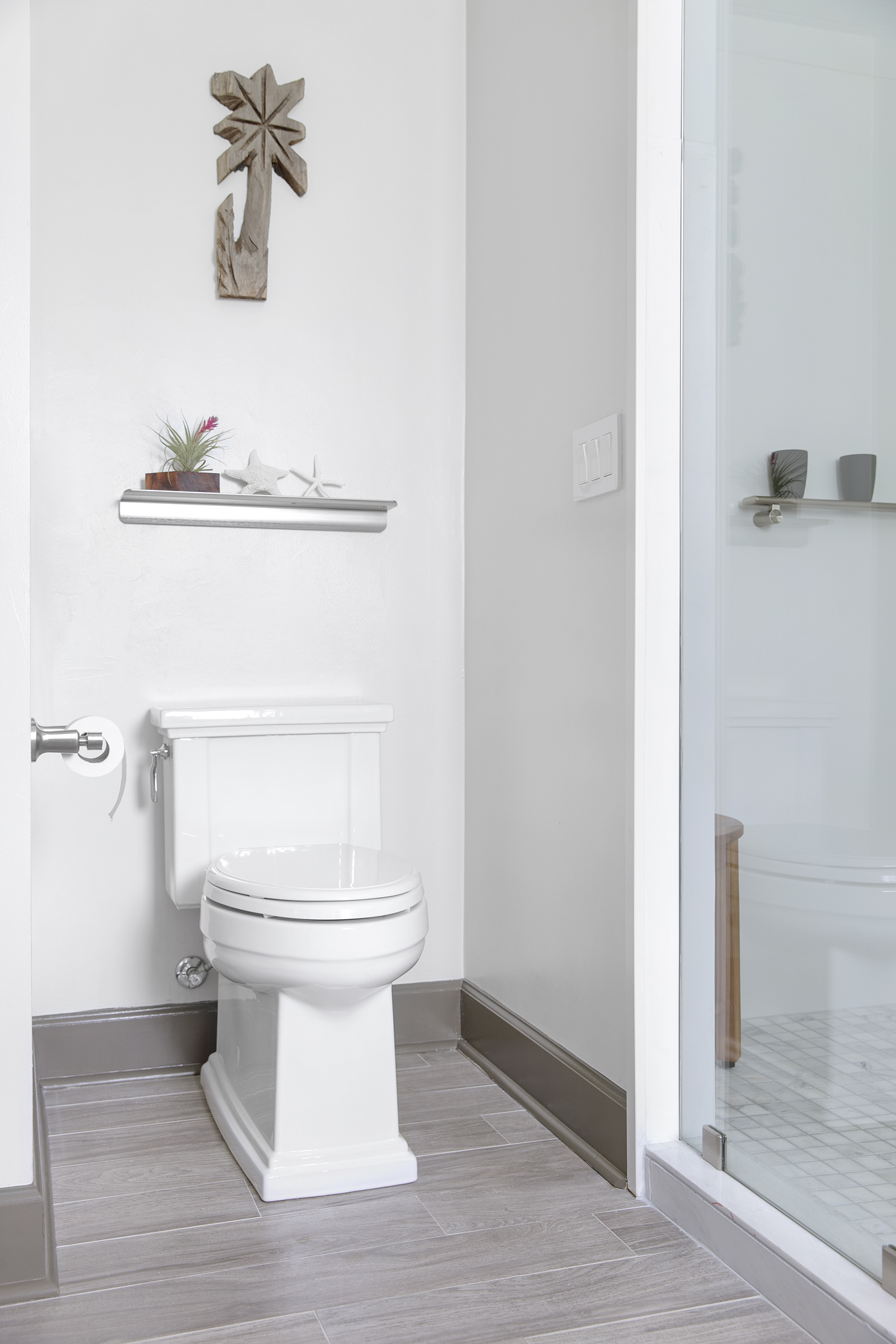 Tresham® toilet   Choreograph® floating shelf     A private nook for the toilet comes to life with a simple shelf and decor that reflects the home's oceanside location.