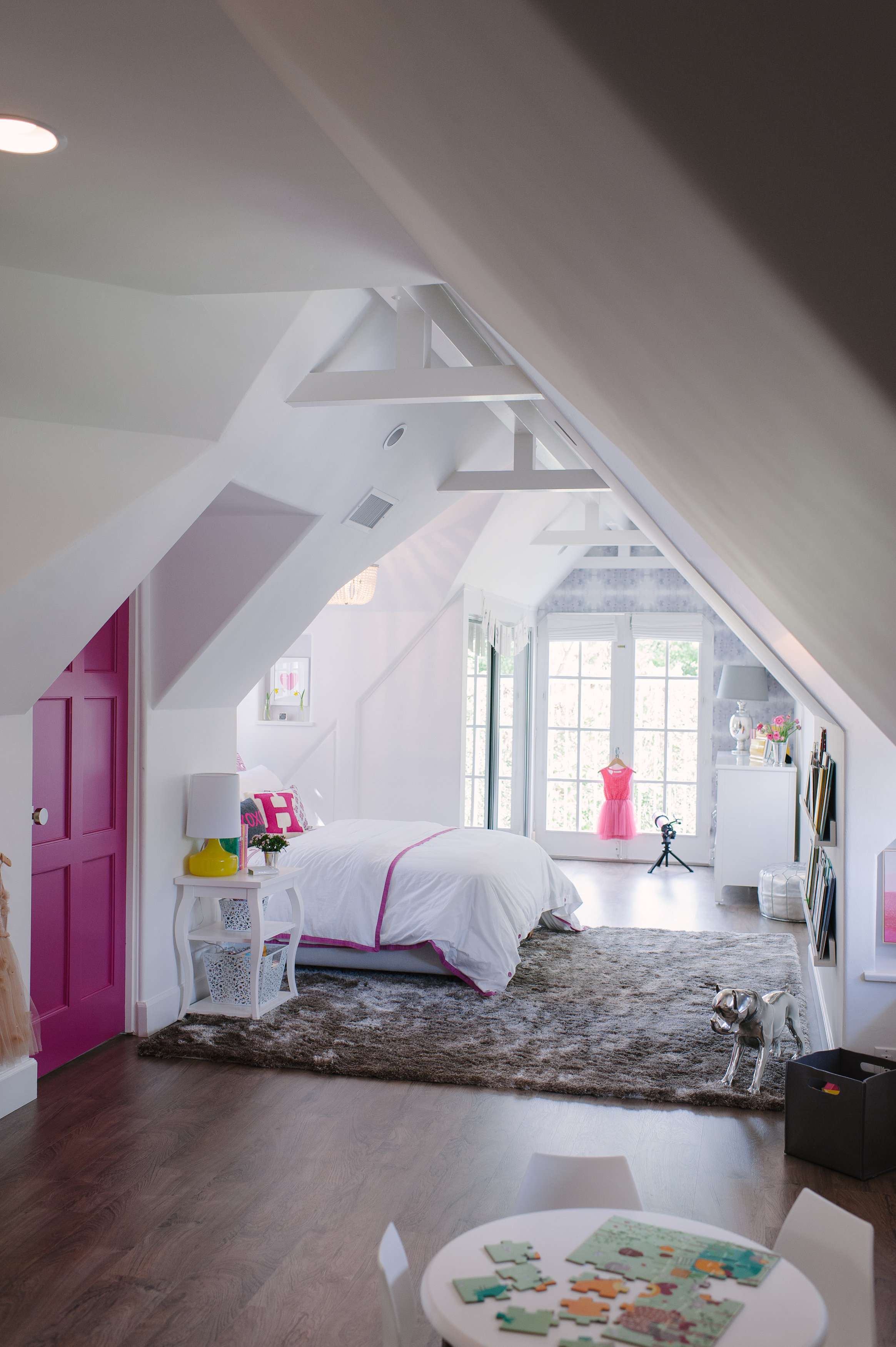 """Six-year-old daughter Harper's room is sweet, but not babyish, with white walls that play up its architectural details and a fun pop of magenta on the door. """"This room has a beautiful little dollhouse vibe now, but it'll be a great space to grow into,"""" says designer Kim Lewis."""