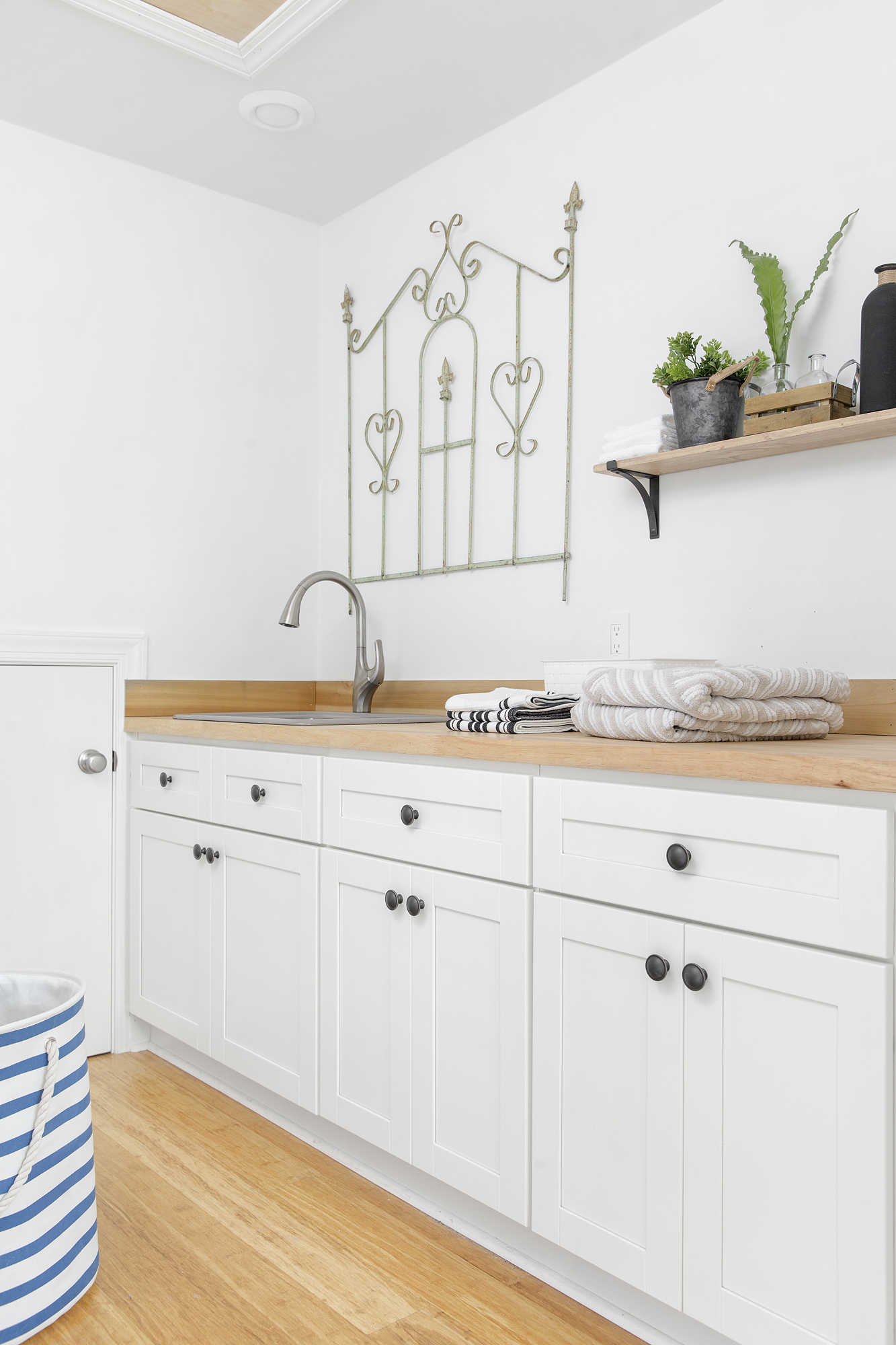 Trielle® pull-down faucet     River Falls™ utility sink     Simple décor and an accent of greenery create visual interest without cluttering the laundry space while a sleek pull-down faucet with multiple sprays is ideal for helping with cleaning tasks.