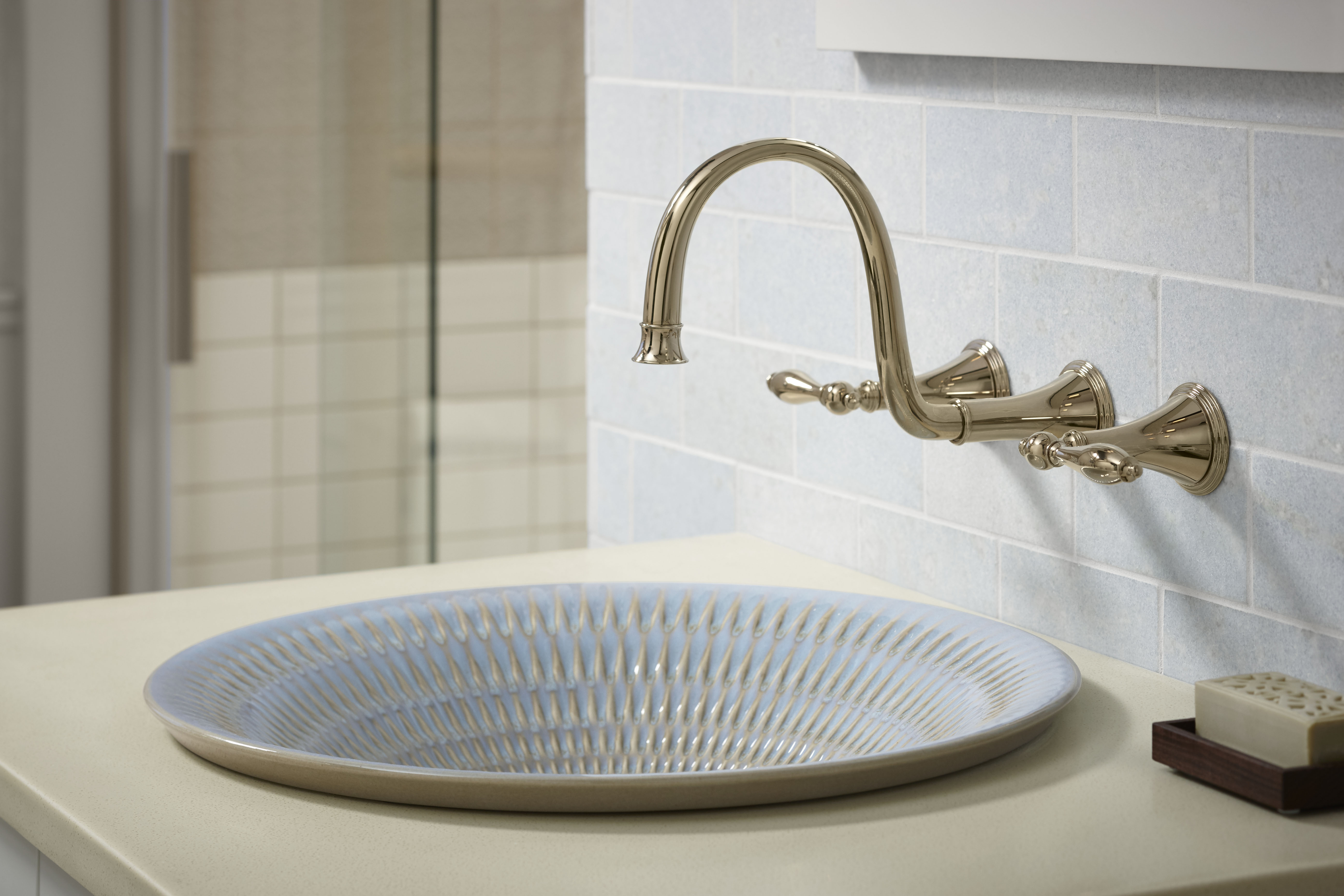 Finial Traditional Faucet     Derring Sink     The subtle warmth of this French Gold wall-mount faucet complements the sink's neutral blue and cream tones.