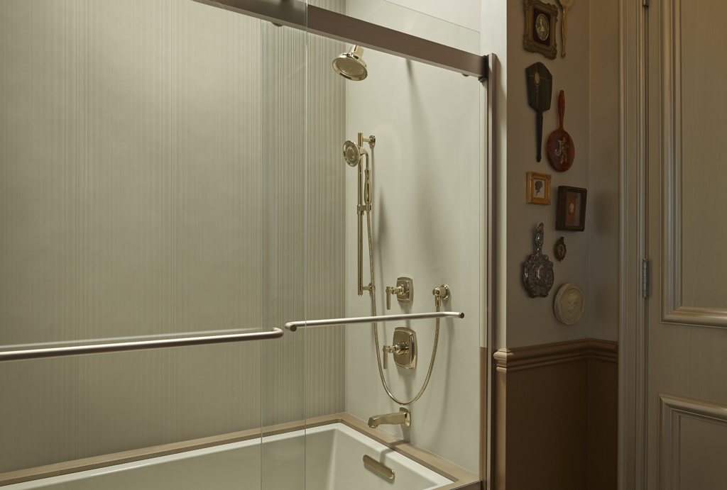Margaux showerhead   Forte handshower   Margaux valve trim   Underscore bath  and  Margaux bath spout   Choreograph wall panel   Gold-finish showering components add unabashed elegance to a smoky bathroom.