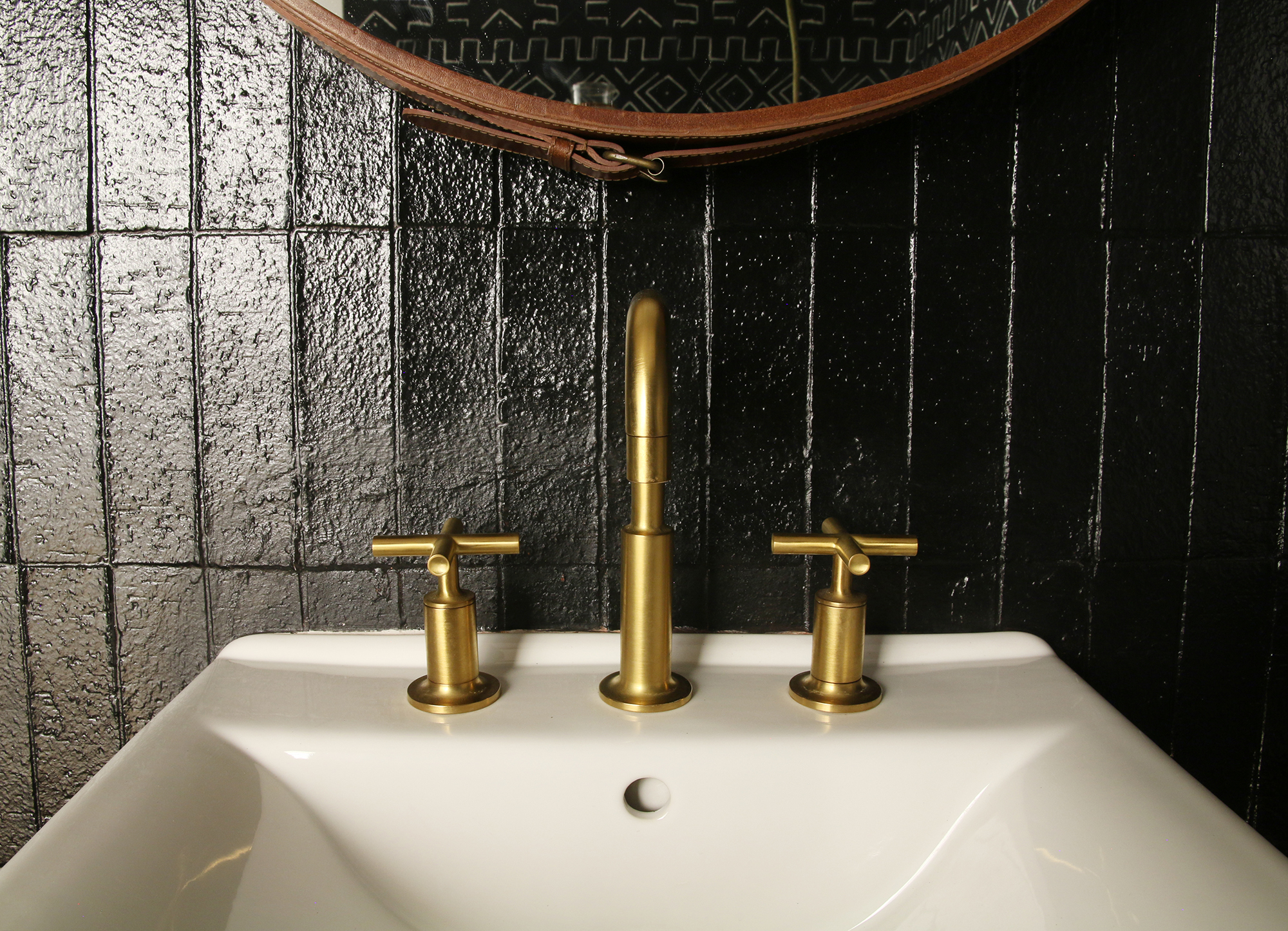 Purist faucet   Soho sink   A gold faucet finish adds richness and understated glamour to a glossy black wall.