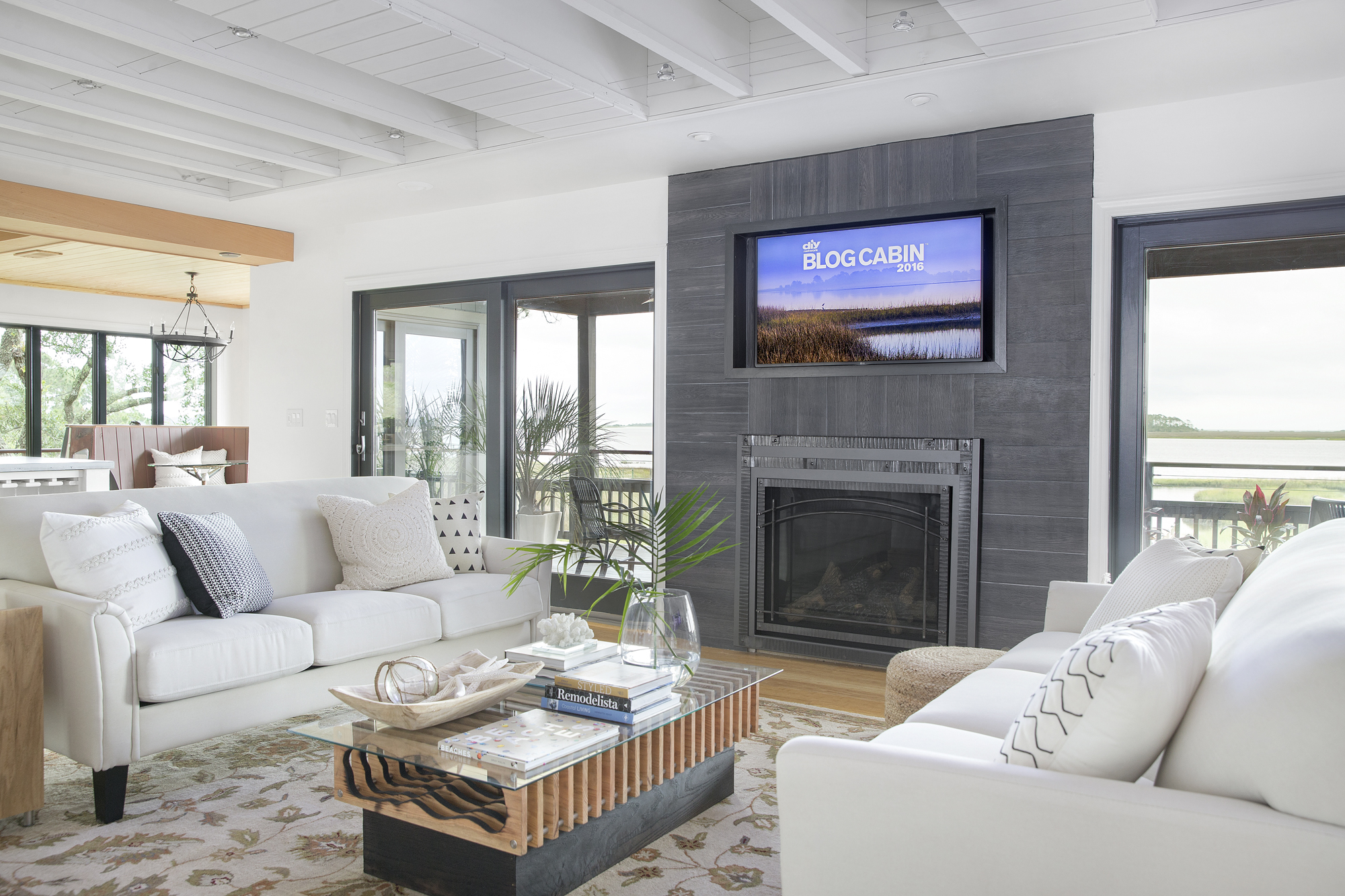 Exposed joists and V-groove ceiling boards in linen white ground the living room in coastal cottage style, while the gray porcelain fireplace surround offers a visual focal point.