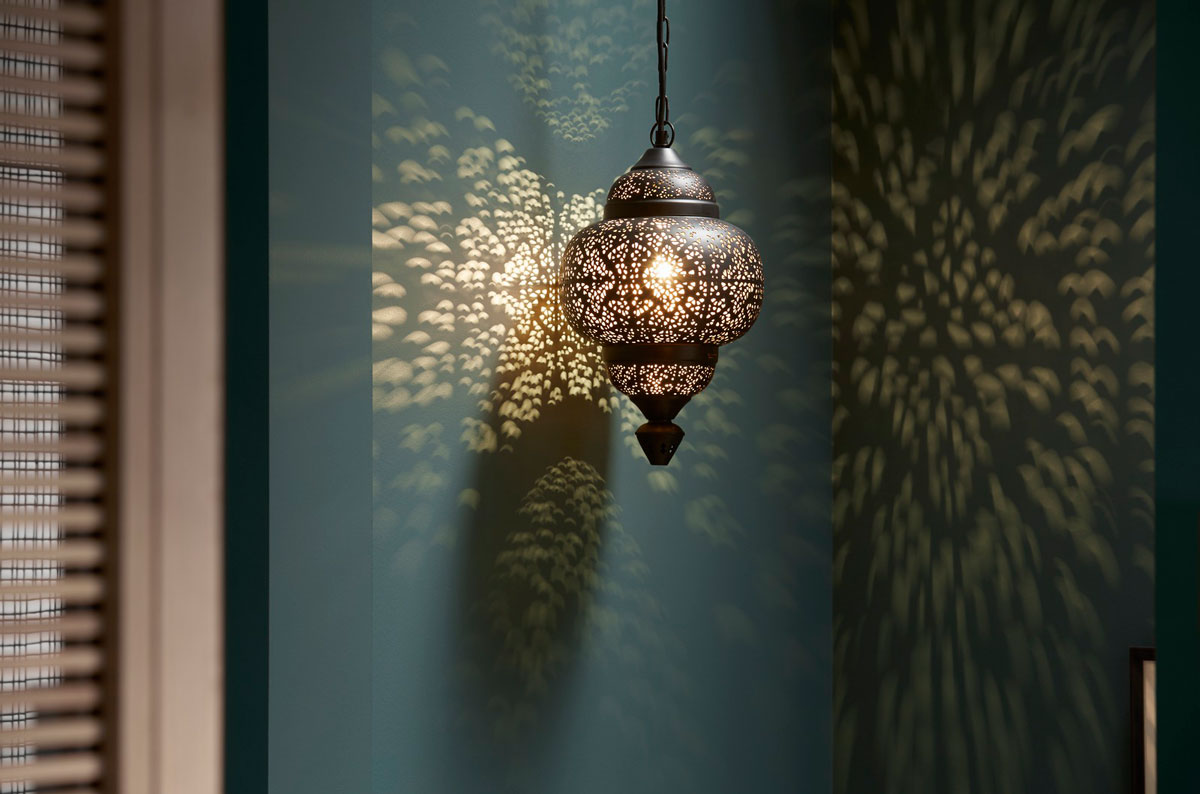 An Indian-inspired pendant light hangs in contrast to the modern chandelier, throwing kaleidoscopic patterns across dark alcove walls.