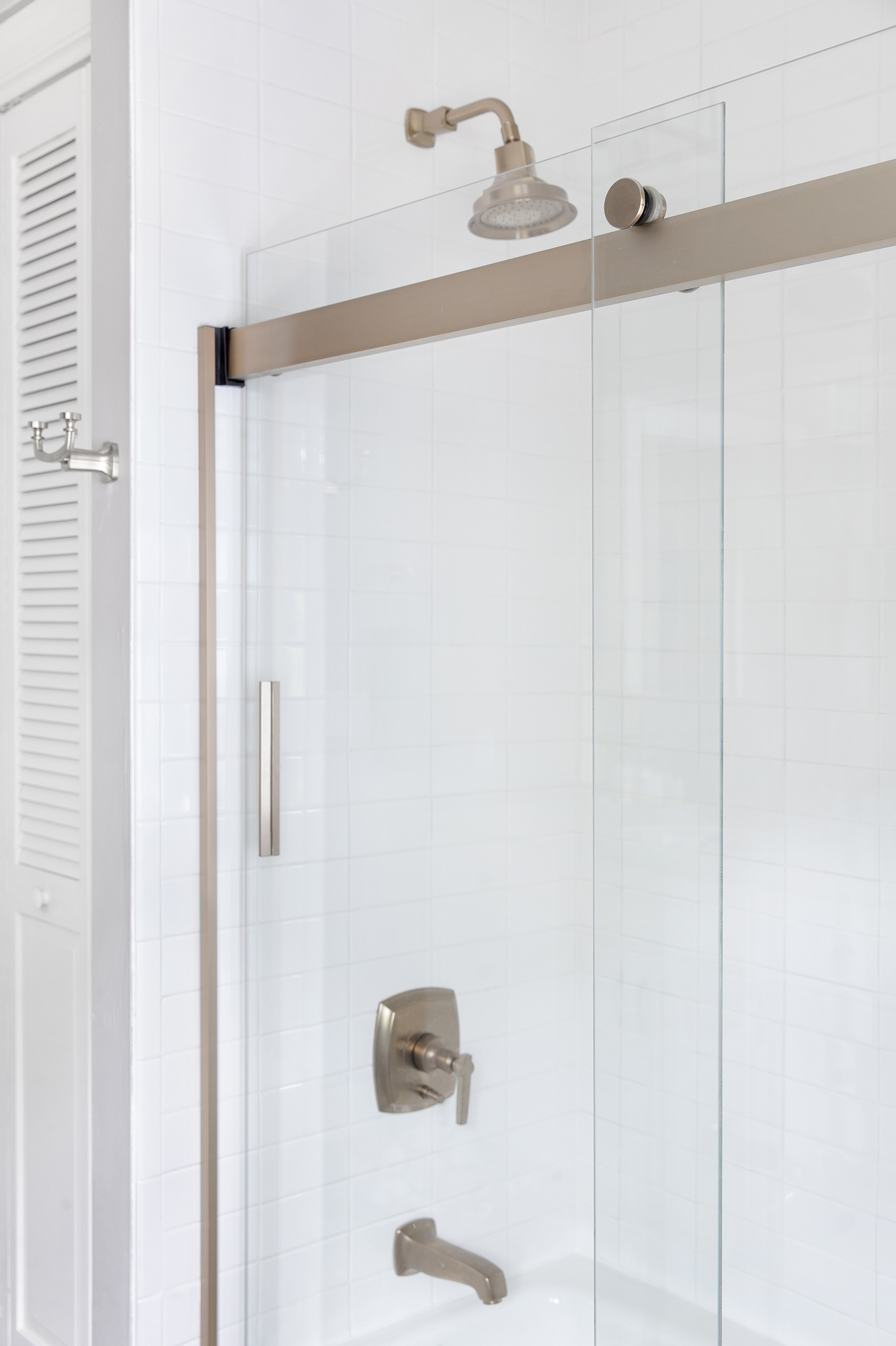 Margaux® bath/shower trim set     Levity® bath door     Villager™ alcove bath     A single brushed bronze finish on all the faucets as well as the shower doors brings a cohesive look to the bathroom.