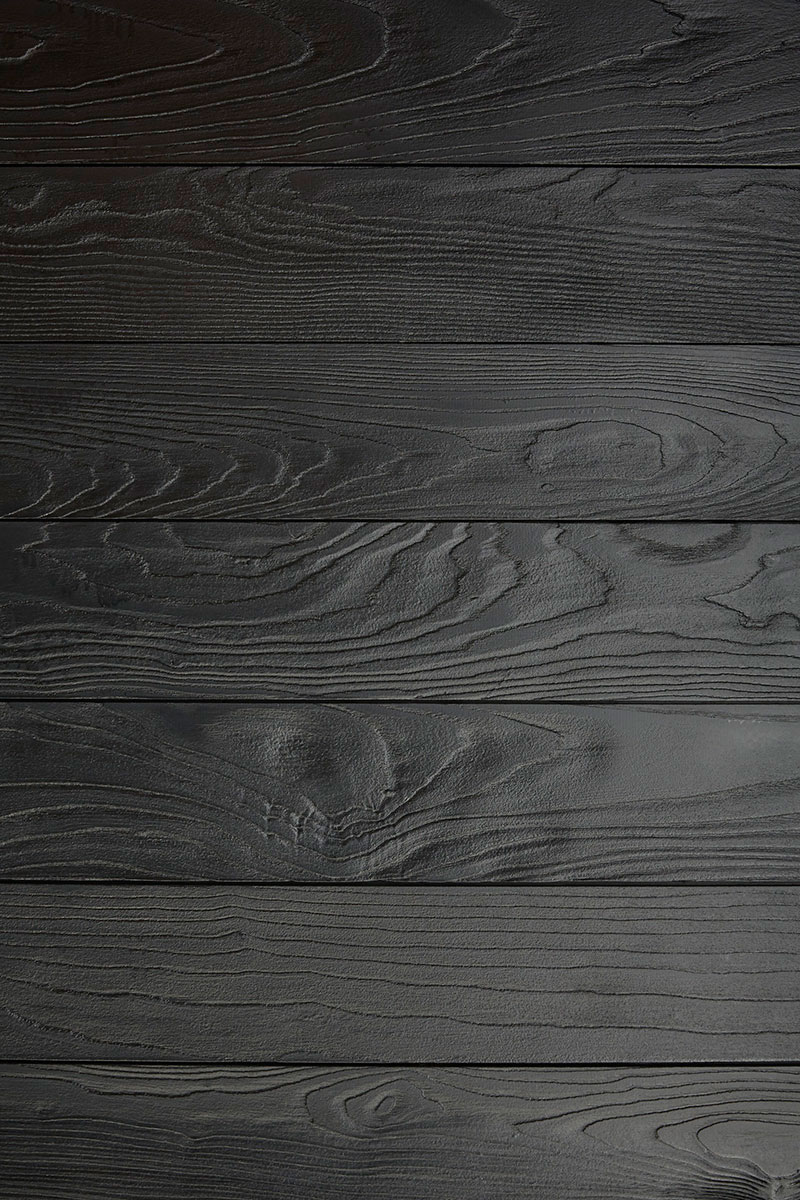 Taking a torch to this paneling brings out an ebony sheen and the grainy texture of this charred wood.
