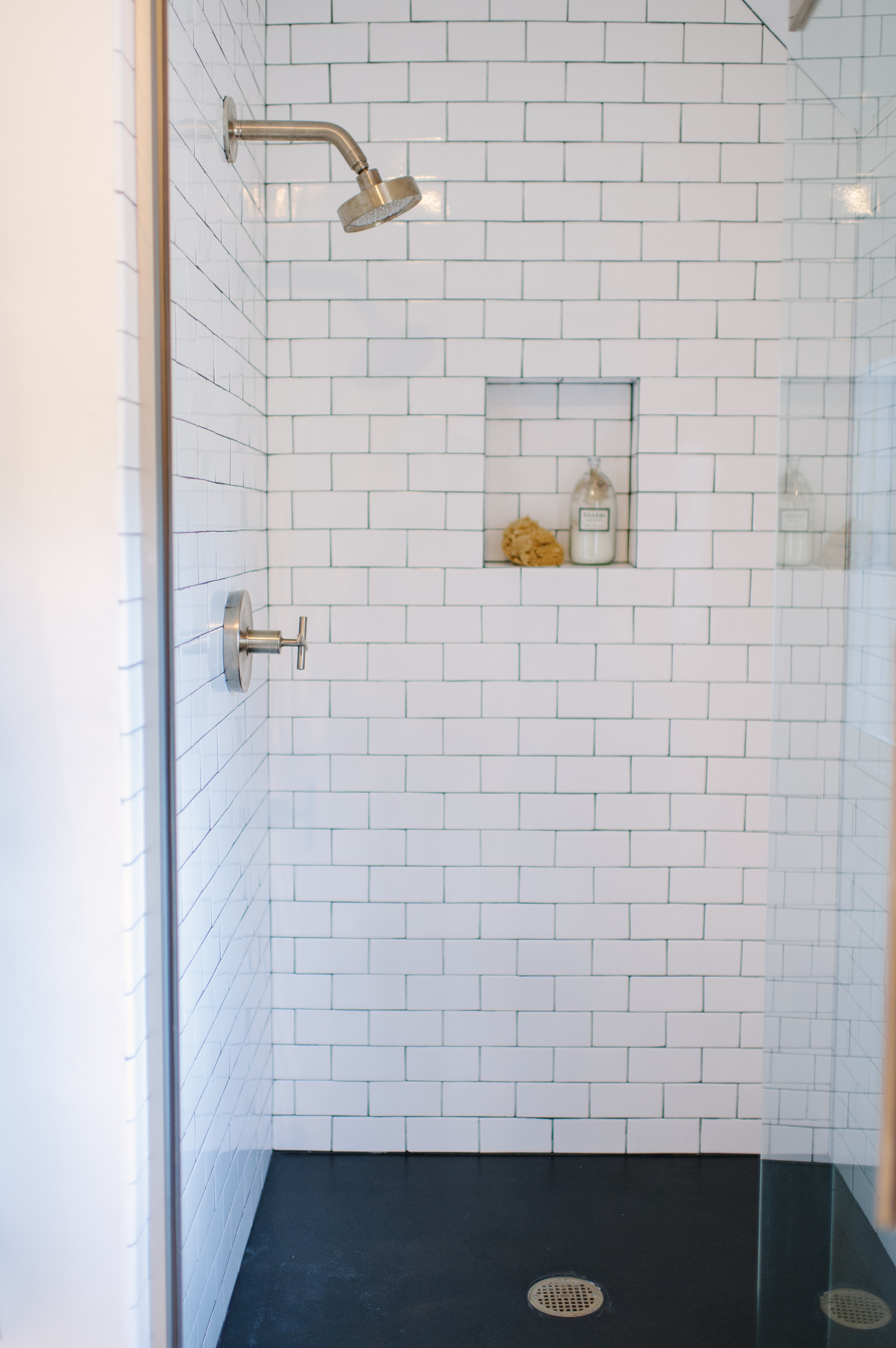 Purist showerhead and trim    Lewis paired a bronze finish on the shower components to glam up the classic white tile in the guest shower.