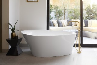 Veil™ freestanding bath    Purist® floor-mount bath filler    The rounded freestanding bath in White creates a sculptural presence that's nicely contrasted by the angular black table next to it.