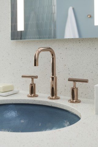 Purist® bathroom sink faucet    Verdera® medicine cabinet    Whist® glass sink    The warm Vibrant® Rose Gold finish and clean modernist lines of the widespread faucet with lever handles balance the cool tones of the undermount glass sink and counter surface.