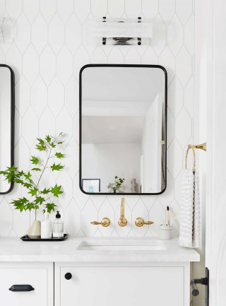 The vanity area uses subtle punctuations of gold, black and green to tell a casually elegant design story.