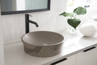 Kensho vessel sink    Components faucet    The etched patterns on the natural stone sink add an organic textural element.