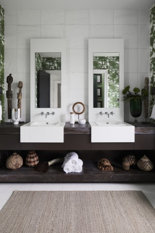 Iron Plains® bathroom sink    Purist® wall-mount bathroom sink faucet    The junior master bath strikes a calming yet invigorating presence, perfectly juxtaposing seemingly contradictory elements: bracing whites and earthy browns, crisp lines and organic shapes, spare minimalism and exuberant maximalism.