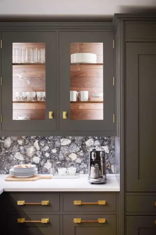 The free-form pastiche of the English flint stone backsplash softens the crisp angularity of the cabinets and countertop.