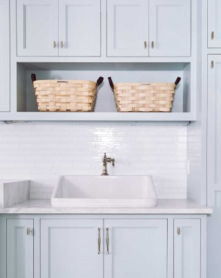 """Hollister utility sink    Artifacts single-handle bathroom sink faucet    A """"happy accident,"""" this utility sink was originally intended to be wall-mounted without the use of cabinets for an apron-front appearance, but it looks perfectly at home just the way it is."""