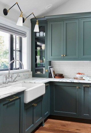 Whitehaven apron-front sink    HiRise faucet    The stark white apron-front sink and Polished Stainless bridge faucet add a curvy, traditional touch that balances the crisp lines of the cabinets and windows.