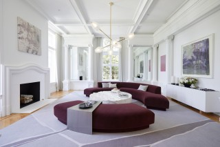 Against a stark white backdrop, this room explores the spectrum of expressions that can be built upon a purple foundation. Note the contrast between the ornate painting and clean simplicity of the sofa.