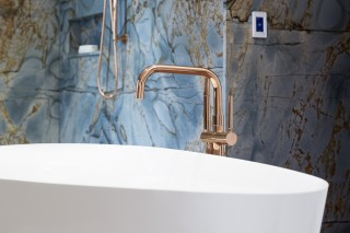 Veil™ freestanding bath    Purist® floor-mount bath filler    A rose gold bath filler provides cohesion throughout the finishes.