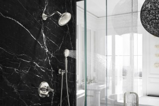 Artifacts® showerhead    Artifacts handshower    Artifacts shower valve trim with swing lever handle    Veined black-marble walls provide a dramatic and free-form counterpoint to the disciplined shapes throughout the rest of the bathroom.