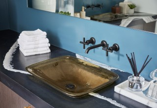 Purist faucet    Inia Wading Pool sink    A translucent glass sink and contemporary matte black faucet contribute to the organic, nautical theme of the bathroom.