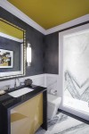 Rêve Toilet    Purist Sink Faucet    Caxton Rectangle Sink   A custom statement vanity in black and gold highlights how bold design can have a large impact even in smaller bathroom spaces.